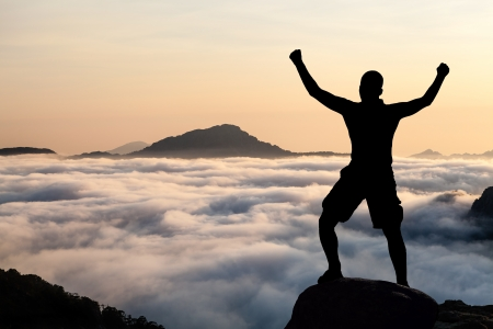 Man hiking silhouette in mountains, sunset and clouds. Male climber hiker arms outstretched on top of mountain after success climbing looking at beautiful sunset sky night landscape. photo