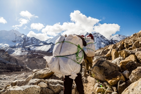 sherpa: Porter and Sherpa walking with big bag baggage luggage in Himalaya Mountains in Nepal. Khumbu glacier in Everest National Park and people trekking on rocky footpath trail. Stock Photo