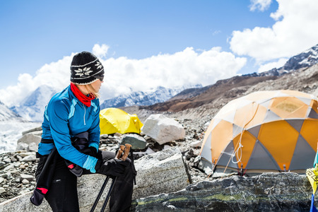 mountaineer: Young woman hiker hiking in Himalaya Mountains in Nepal, Mount Everest Base Camp at 5350m a.s.l on Khumbu glacier camping site
