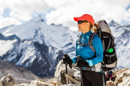 Young woman hiker hiking in Himalaya Mountains in Nepal. Trekking sport and fitness outdoors in high mountains Everest Nationa Park Khumbu glacier. Banco de Imagens