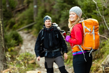 Man and woman hikers trekking in mountains. Young couple walking with backpacks in forest, Tatra Mountains in Poland. Trekking hiking outdoors in beautiful nature