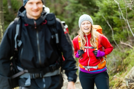 Man and woman hikers trekking in mountains. Young couple walking with backpacks in forest, Tatras in Poland. Trekking hiking outdoors in beautiful nature Banco de Imagens