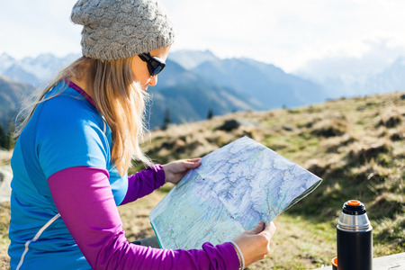 Young woman hiker reading map in mountains on hiking trip  Stock Photo