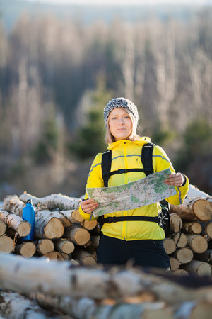Woman hiking in forest reading map. Recreation and healthy\ lifestyle outdoors in nature. Beauty blond looking at camera on\ sunset.