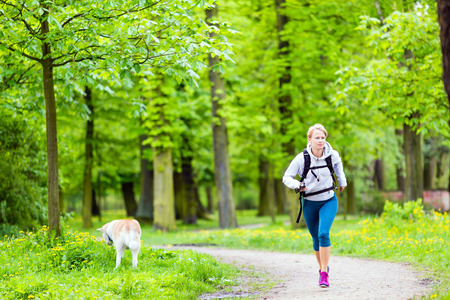 Woman runner running and walking with dog in park, summer nature, exercising in bright forest outdoors photo
