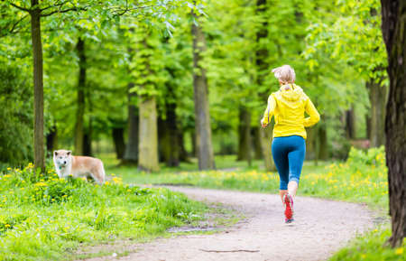 Woman runner running with dog in park, summer nature, exercising in bright forest outdoors photo