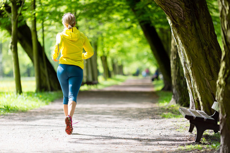 Woman runner running and walking in park, summer nature, exercising in bright forest outdoors photo