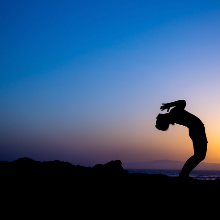 Young woman doing yoga, sunset silhouette in mountains and sea photo
