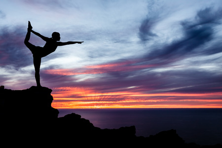 Young woman doing yoga, sunset silhouette in mountains over ocean and sky
