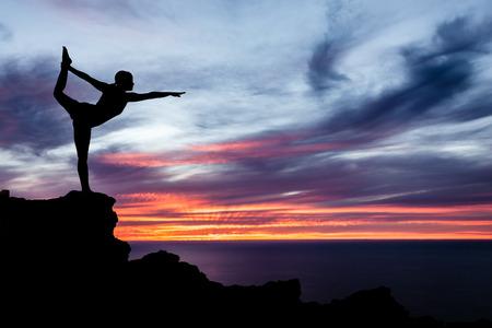 Junge Frau, die Yoga, Sonnenuntergang Silhouette in den Bergen über Meer und Himmel Lizenzfreie Bilder