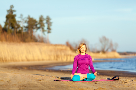 bliss: Young woman doing yoga near lake outdoors, meditation. Sport fitness and exercising in nature, autumn sunset