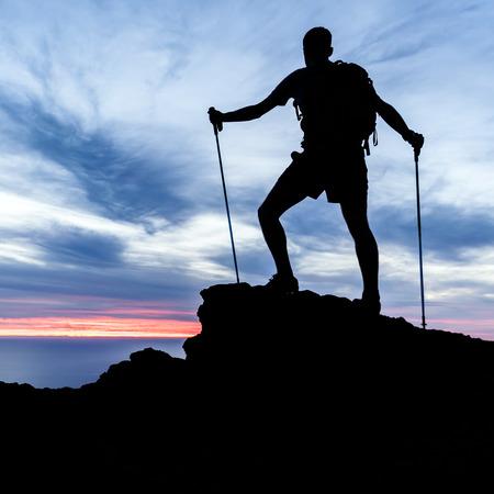 Mann, Wandern in den Bergen Silhouette, Sonnenuntergang und das Meer. Männlich Wanderer mit Wanderstöcken auf der Berg Blick auf schöne Nacht Landschaft. Lizenzfreie Bilder