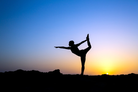Young woman doing yoga, sunset silhouette in mountains photo