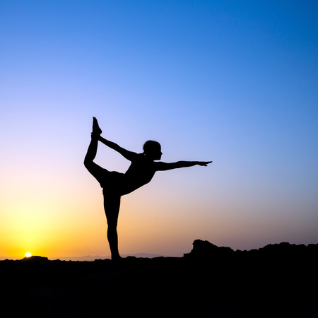 Young woman doing yoga, sunset silhouette in mountains