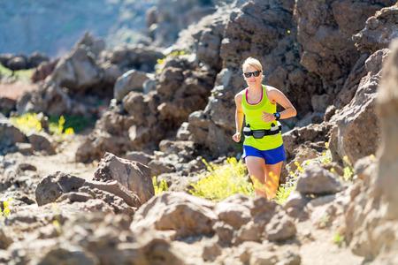 Junge Frau in den Bergen läuft an sonnigen Sommertag. Beauty weibliche Läufer joggen und trainieren draußen in der Natur, felsigen Weg Fußweg auf La Palma, Kanarische Inseln Lizenzfreie Bilder