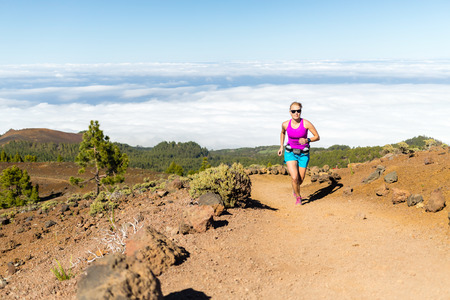 Young woman trail running in mountains on sunny summer day. Beauty female runner jogging and exercising outdoors in nature, rocky trail footpath on La Palma, Canary Islands photo