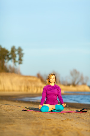 Young woman doing yoga near lake outdoors, meditation. Sport fitness and exercising in nature, autumn sunset photo