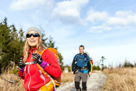 woman hiking: Man and woman hikers hiking on mountain trail autumn or winter nature  Young couple backpackers walking in forest landscape  Happy trekkers on travel trip with backpacks, camping outdoors