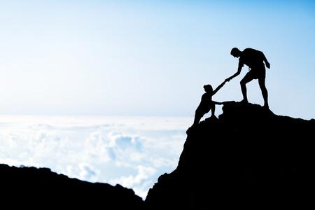 커플 하이킹 도움이 산에서 서로 실루엣, 등산의 상단에 서로 돕는 일몰 및 바다에 남성과 여성 등산객, 아름다운 일몰 풍경