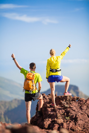 Man and woman hikers trekking or trail running in summer mountains  Young couple on rocky mountain range looking at beautiful view  photo