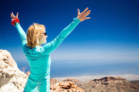 Hiking woman and success in mountains  Fitness and healthy lifestyle outdoors in summer nature  Trail runner beautiful female with arms outstretched on island, sea ocean in background, Tenerife Canary Islands over blue clear sky  Stock Photo