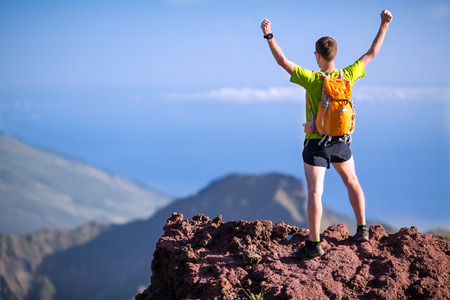 mountaineering: Hiker or trail runner man and success in mountains  Fitness and healthy lifestyle outdoors in summer nature, climbing mountaineering Stock Photo