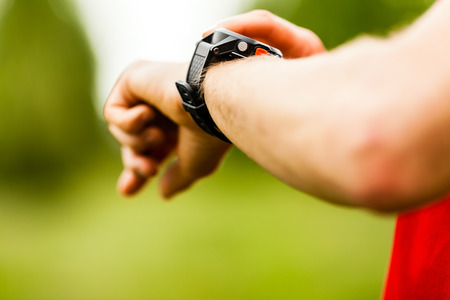 taking pulse: Trail or cross country runner on mountain path looking at sportwatch, checking performance or heart rate pulse  Goal achievement, sport and fitness concept outdoors in nature  Stock Photo
