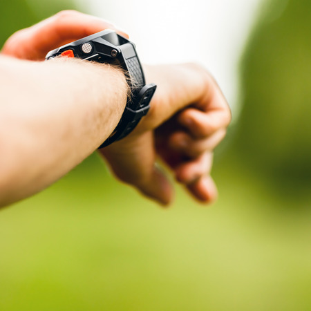 Trail or cross country runner on mountain path looking at sportwatch, checking performance or heart rate pulse  Goal achievement, sport and fitness concept outdoors in nature  photo