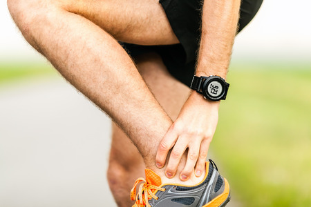 leg injury: Runner holding sore leg, knee pain from running or exercising, jogging injury or cramp, cross country in summer nature