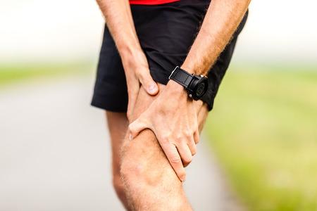 cramp: Runner holding sore leg, knee pain from running or exercising, jogging injury or cramp, cross country in summer nature