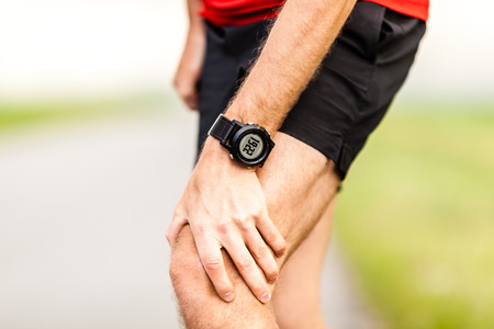 sports injury: Runner holding sore leg, knee pain from running or exercising, jogging injury or cramp, cross country in summer nature