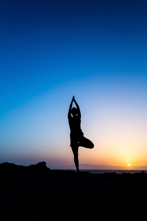 Young woman doing beautiful yoga pose tree, sunset silhouette in mountains over blue sky and clouds with sun sunlight background  Healthy lifestyle successful fitness exercise concept  photo