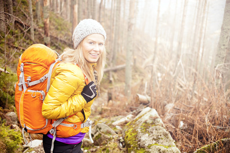 Woman hiking in autumn forest in mountains  Trekking, recreation and healthy lifestyle outdoors in nature  Beauty blond backpacker looking at camera smiling, bright light sunlight in background  Banco de Imagens