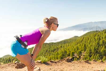 Young woman cross country running in mountains on sunny summer day  Beauty female runner jogging and exercising outdoors in nature, rocky trail footpath on La Palma, Canary Islands photo