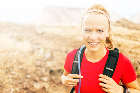 Young woman trail running in mountains on sunny summer day  Female runner exercising outdoors in nature, sunset  Cross country working out, sport and fitness concept  photo