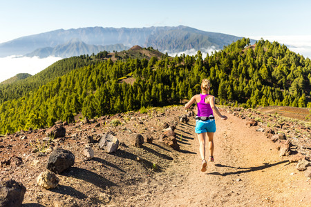 Young woman cross country running in mountains on sunny summer day  Beauty female runner jogging and exercising outdoors in nature, rocky trail footpath on La Palma, Canary Islands