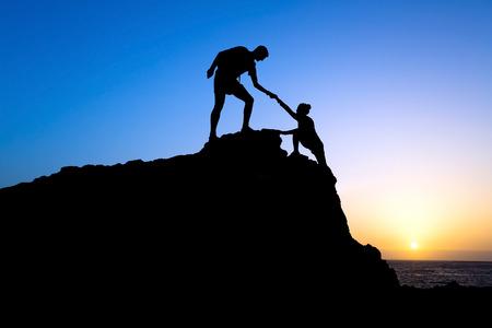 Paar wandelen help elkaar silhouet in de bergen, zonsondergang en de oceaan Man en vrouw wandelaar helpen elkaar op de top van berg beklimmen, prachtige zonsondergang landschap Stockfoto