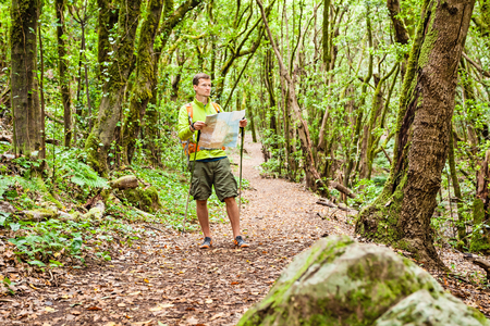 magical equipment: Man hiker hiking in green forest  Young male looking at map and planning trip or get lost in green beautiful magical forest, La Gomera, Canary Islands