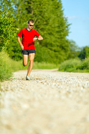 heartrate: Man runner running on country road in summer sunset  Checking pulse trace on heartbeat monitor  Young athlete male training and doing workout outdoors in nature  Stock Photo