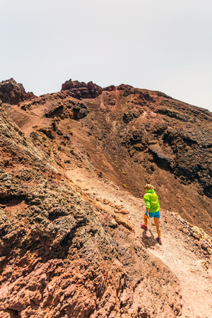 Young woman trail running or hiking in mountains on sunny summer day  Beautiful landscape and female runner jogging and exercising outdoors in nature, rocky trail footpath on La Palma, Canary Islands photo