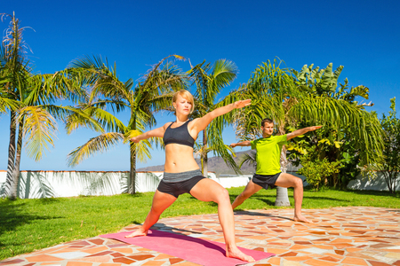 Young couple doing beautiful yoga pose outdoors in summer sunny nature, warrior one position, group training and stretching  Fitness and exercising in fresh green garden over blue sky photo