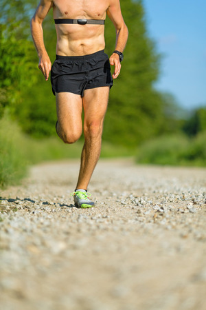 Man runner running on country road in summer sunset  Young athlete male training and doing workout outdoors in nature  Checking pulse trace heartbeat using gps watch photo