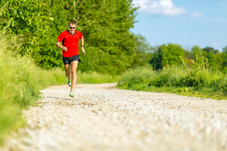 Man runner trail running on country road in summer sunset  Young athlete male cross country training and doing workout outdoors in green nature, summer blue sky photo