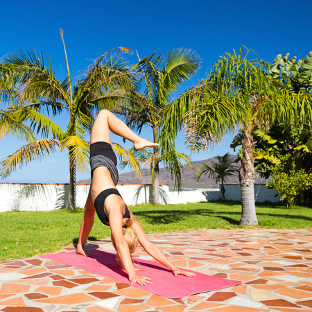 Woman doing yoga pose outdoors in beautiful summer sunny nature, leg extended downward dog position  Fitness and exercising in fresh green garden over blue sky photo