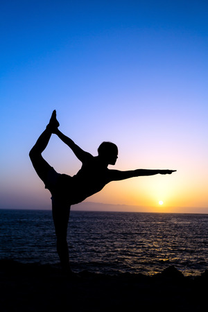 Young woman doing yoga pose king dancer, sunset silhouette in mountains and sea ocean  Sport and exercising in beautiful nature outdoors photo