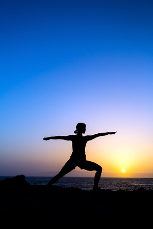 Young woman doing yoga pose warrior one, sunset silhouette in mountains  Sport and exercising in beautiful nature outdoors photo