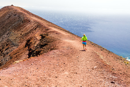 Young woman running in mountains on sunny summer day  Beautiful landscape sea ocean and female runner jogging and exercising outdoors in nature, rocky trail footpath on La Palma, Canary Islands Spain photo