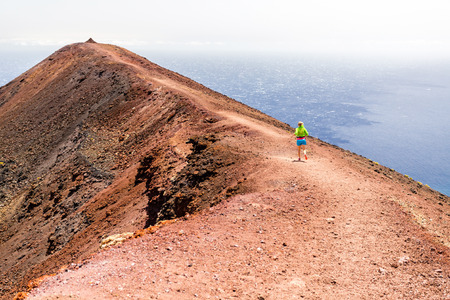 Young woman running in mountains on sunny summer day  Beautiful landscape sea ocean and female runner jogging and exercising outdoors in nature, rocky trail footpath on La Palma, Canary Islands Stock Photo