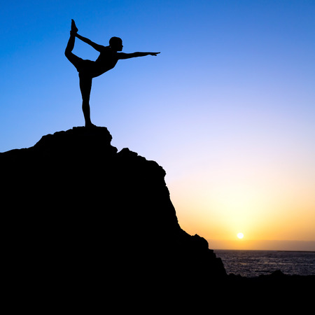 Young woman doing beautiful yoga pose king of the dancer, sunset silhouette in mountains over blue sky and clouds with sun sunlight background. Healthy lifestyle successful fitness exercise concept. Banco de Imagens