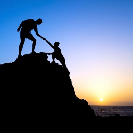 personas ayudando: Pareja de senderismo se ayudan mutuamente silueta en las montañas, puesta del sol y el océano. Caminante masculino y mujer ayudarse unos a otros en la parte superior de la escalada de montaña, paisaje hermoso atardecer.